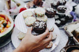 """photo credit: marcoverch <a href=""""http://www.flickr.com/photos/149561324@N03/30472832078"""">Hand nimmt ein Schoko-Cupcake. Tisch mit Nachspeisen im Hintergrund</a> via <a href=""""http://photopin.com"""">photopin</a> <a href=""""https://creativecommons.org/licenses/by/2.0/"""">(license)</a>"""